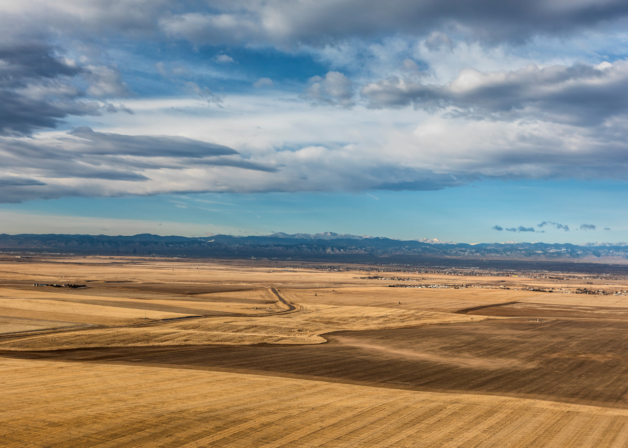 open fields with mountains in the background